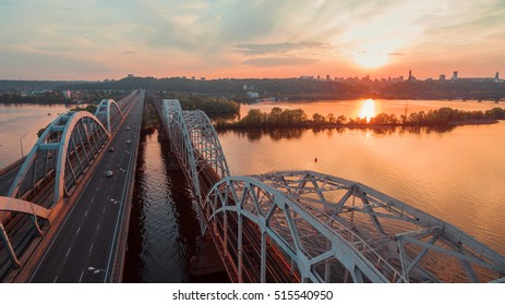 Automobile and railroad bridge in Kiev, the capital of Ukraine. Bridge at sunset across the Dnieper River. Kiev bridge against the backdrop of a beautiful sunset in Kiev. Bridge in evening sunshine.