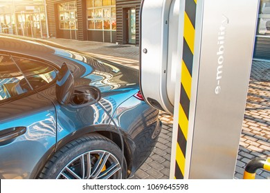 Automobile refueling for electric cars e-mobility in the background e-car, wheel. Charging e-car, the fuel cell battery door is open