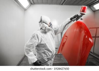Réparateur d'automobiles peintre en masque et carrosserie de protection de la voiture peintre dans la chambre de peinture.