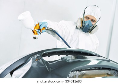 automobile repairman painter in protective workwear and respirator painting car body bumper in paint chamber