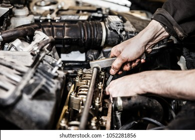 Automobile service worker or garage mechanic hand holding vehicle motor maintenance tool repairing auto car engine