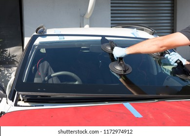 Automobile special workers glazier replacing windscreen windshield of car in street or work place