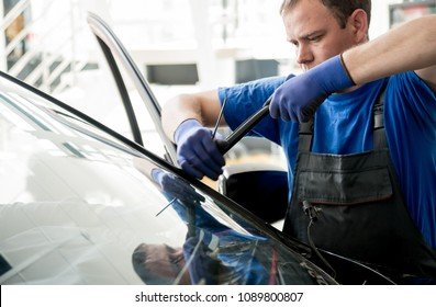 Automobile special workers remove old windscreen or windshield of a car in auto service station garage. Background