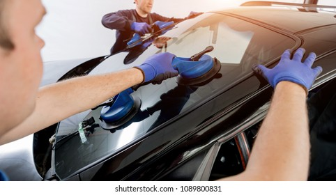 Automobile special workers replacing windscreen or windshield of a car in auto service station garage. Background