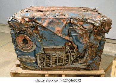 An automobile that has been crushed and compacted into the shape of a box for disposal or recycle.