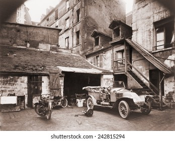 Automobile and two motorcycles in courtyard on Rue de Valence, Paris, photographed by Eugene Atget with a large-format wooden bellows camera. Ca. 1920.