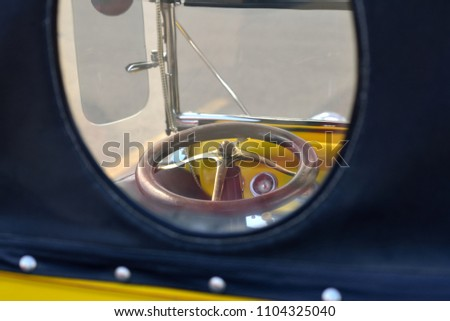 Automobile: vintage roadster steering wheel seen through vehicle's oval rear window