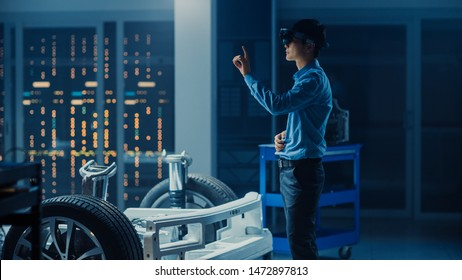 Automotive Engineer Working on Electric Car Chassis Platform, Using Augmented Reality Headset with Touching Gestures. In Innovation Laboratory Facility Concept Vehicle Frame with Wheels