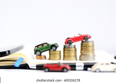 Automotive industry evolution concept with colored toy cars on pile of coins