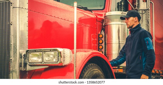 Automotive industry. Modern Truck Transportation. Caucasian Trucker in Front of His Red Shiny Truck.