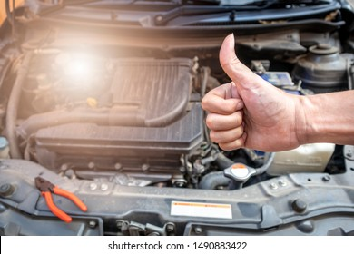 Automotive mechanic show a thumbs up after the car check and repair in workshop.