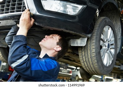automotive mechanic worker examining car bottom during automobile car maintenance at lever repair service station
