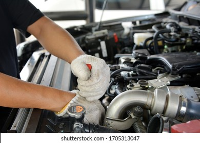 Automotive mechanic working in garage. Repair service. Mechanic working on a diesel engine, close up. Technician hands of car mechanic in doing auto repair service and maintenance worker repairing.