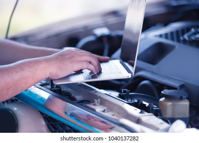 Automotive mechanical technician using laptop computer promgraming and  investing by car diagnostic software, car maintenance service concept.