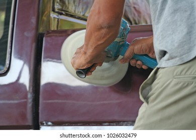 Automotive paint technician using grinder machine with wax on  side of pickup  , A part of the procedure to make a new color car