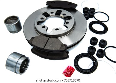 Automotive Spare Parts of disk brake pads, disc brake caliper piston, disk brake repair kIt and rotating brake disk on white background.