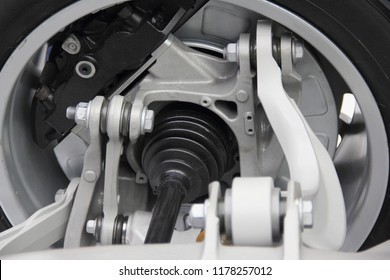 Automotive transmission parts - close up driveshaft, tripod CV-joint, brake caliper unit, levers, disk and tire of new concept car