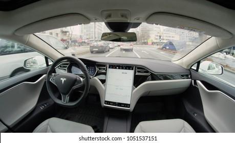 AUTONOMOUS TESLA CAR, FEBRUARY 2016: Fully autonomous self-driving autopilot Tesla Model S driverless car maneuvering on local street in urban city. Enhanced next gen intelligent robotic vehicle