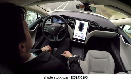 AUTONOMOUS TESLA CAR, FEBRUARY 2016:  Young businessman traveling to work in luxury Tesla Model S car with enabled autopilot automated self-driving system. Electric vehicle driving on the road by itse