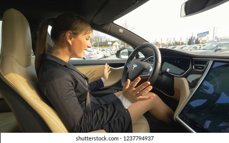 AUTONOMOUS TESLA CAR, MARCH 2018 - CLOSE UP: Caucasian woman is amazed at autonomous car parking itself without her control. Young businesswoman is excited to see her car self park into an empty spot.