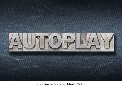 autoplay word made from metallic letterpress on dark jeans background