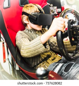 AUTOSHOW PRAHA, CZ - OCT 7, 2017: Virtual reality glasses in car video game. Boy with black Oculus VR RIFT or GO headset sits in moving sportscar seat, holds steering wheel, drives in unreal 3d space.