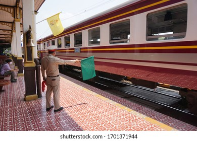 Autthaya/Thailand-April11,2020:Green flag is raised up and waved by train staff to be safety signal to driver officer start running to depart station , some passenger wearing mask in background.