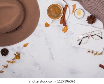 Autumn accessories flat lay. Hat, coffee, glasses and yellow leaves