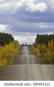 Autumn along the adventurous rise and fall of Cassiar-Stewart Highway in British Columbia. Vertical photograph with copy space in sky. Rambling road travel symbol.  Date is September 6, 2015.