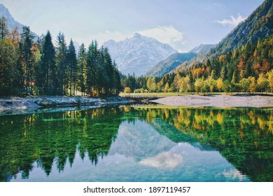 Autumn alps mountains in day light reflected in calm waters of lake Jasna, Kranjska Gora.