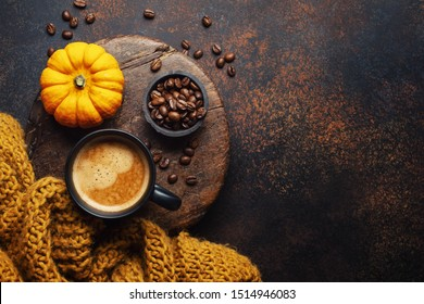 Autumn arrangement with coffee and pumpkin on dark background. View from above.