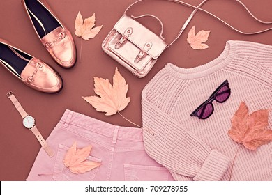 Autumn Arrives. Fashion Lady Clothes Set. Trendy Cozy Jumper. Stylish Gold Handbag Clutch, Glamour Sunglasses. Flat lay. Fall Leaves. Vanilla Pastel colors.