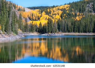 Autumn aspens among evergreens surrounding one of the Mesa Lakes on the Grand Mesa in western Colorado