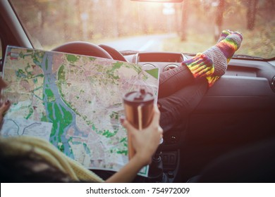 Autumn, Auto travel. Cose-up of a woman drinking take away cup coffee during the road trip in a car. The driver checks the paper map. Woman feet in warm socks on car dashboard.