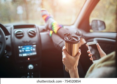Autumn, Autotravel. Cose-up of a woman drinking take away cup coffee during the road trip in a car. Woman feet in warm socks on car dashboard. Drinking take away coffee and using a smartphone on road