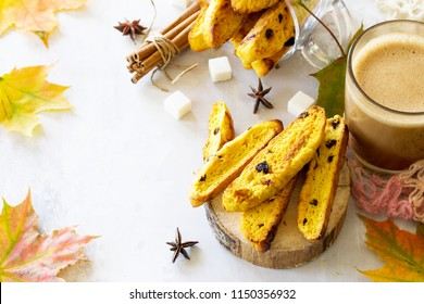 Autumn background baking. Freshly baked raisins and cinnamon biscotti and a cup of cappuccino coffee on light slate or slate background. Copy space.