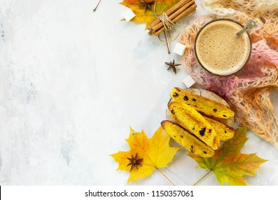 Autumn background baking. Freshly baked raisins and cinnamon biscotti and a cup of cappuccino coffee on light slate or slate background. Top view flat lay background, copy space.
