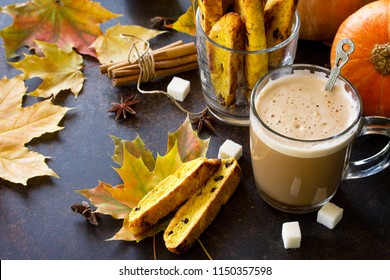 Autumn background baking. Freshly baked raisins and cinnamon biscotti and a cup of cappuccino coffee on a brown slate or slate background. Copy space.