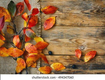 autumn background branch with red yellow leaves, canvas cloth on old wooden board table