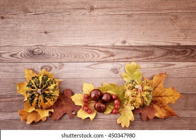 Autumn background. Color leaves on wood background. Fall card with pumpkins.