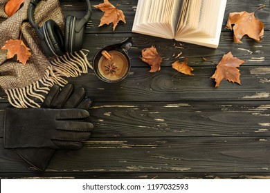 Autumn background. Cup of coffee, lambswool scarf, leather gloves, headphones, open book, maple leaves on black wooden background. Horizontal. Top view.