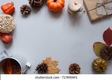 Autumn background. Cup of tea and autumn decoration on gray background. Copy space.