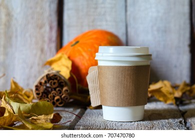 Autumn background with dry leaves and hot paper cup of coffee on wooden table