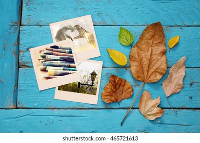 Autumn background with dry leaves and old photo frames on blue wooden table