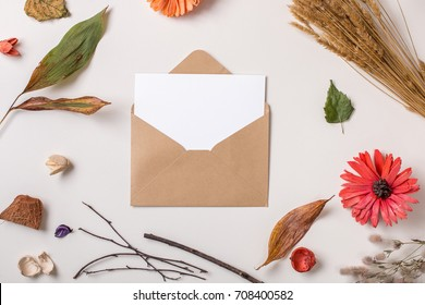 Autumn background: fallen leaves, dry petals, dried flowers and plants with  blank stationary template / invitation mock up / empty paper card in craft rustic envelope on white. Top view. Flat lay.