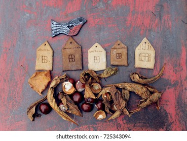 autumn background / figures of houses and bird with  chestnut dry leaves and chestnuts  on the rusty background
