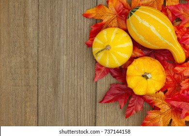 Autumn background with gourds and fall leaves on weathered wood with copy space for your message
