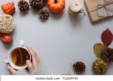 Autumn background. Hands holding cup of tea, autumn decoration on gray background. Copy space