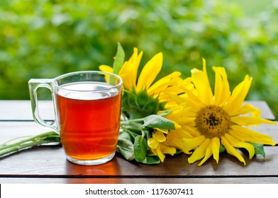 Autumn background, hot tea in a glass and yellow sunflowers with apples on a wooden table. The concept of harvest, autumn.