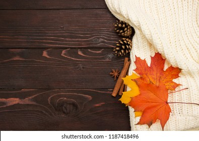 Autumn background. Knitted sweater, autumn leaves , cones and cinnamon sticks on brown wooden board.
